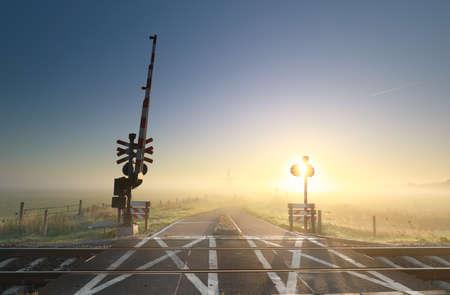 foggy sunrise over railway crossing on Dutch farmland