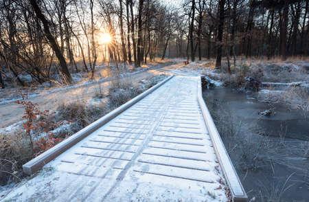 wooden road bridge in winter forest at sunrise Banco de Imagens