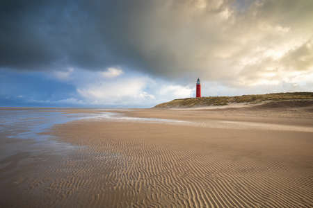 stormy sky over North sea beach with red lighthouse, Texel, Netherlands Stockfoto