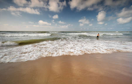 man is swimming in North sea waves in summer