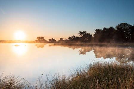 beautiful misty sunrise over forest lake