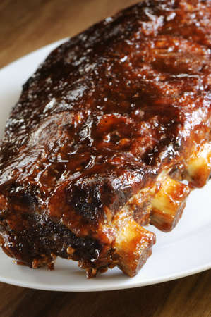 Grilled juicy barbecue pork ribs in a white plate, selective focus  Imagens