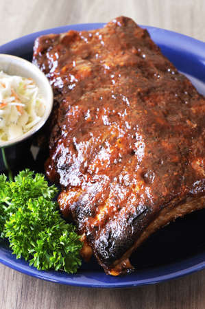 Grilled juicy barbecue pork ribs in a blue plate with coleslaw and parsley.