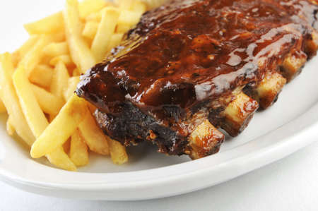 barbecue ribs: Grilled juicy barbecue pork ribs in a white plate with fries  Stock Photo