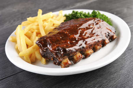 Grilled juicy barbecue pork ribs in a white plate with fries and parsley. photo