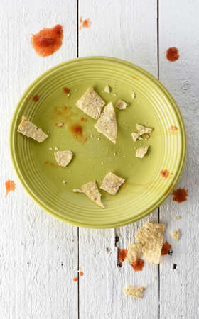 Empty and messy plate of nachos with salsa and tortilla chips crumbs Imagens