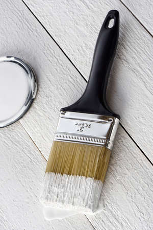 Paintbrush with white paint and can cover on a white background Imagens