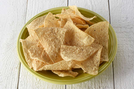 Green flat full of tortilla chips on a white background Imagens