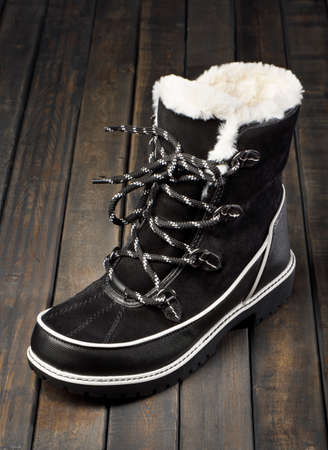Black and white winter boot made of suede and fur on a wooden background