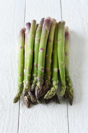 Raw green asparagus on a white background