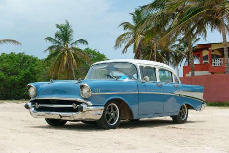 Vintage blue american car on the beach of Cuba