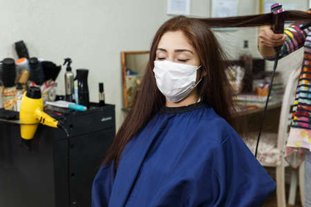beautiful young woman with red hair at the hairdresser's during quarantine and social distancing as a result of covid-19