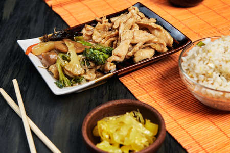 Chinese food served on an oriental plate with soy sauce, chilli and chopsticks on an orange tablecloth and a dark wooden board, ethnic food concept Imagens