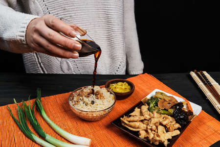 hand pouring soy on rice in a Chinese food dish with chicken and vegetables along with chili on an orange tablecloth on a dark wooden board, ethnic food concept Stok Fotoğraf