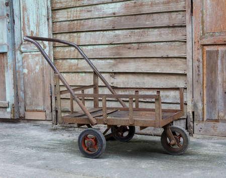 carretilla de mano: Carro viejo oxidado con un telón de fondo de pared de madera