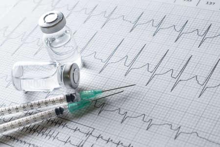 ampules: medical ampules and syringe on EKG graph background Stock Photo