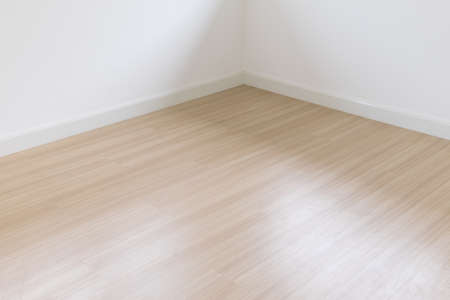 White wall with a hardwood wooden floor