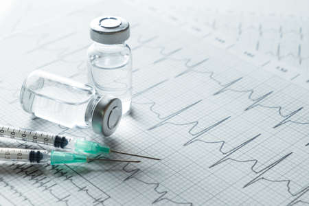 medical ampules and syringe on EKG graph background 免版税图像