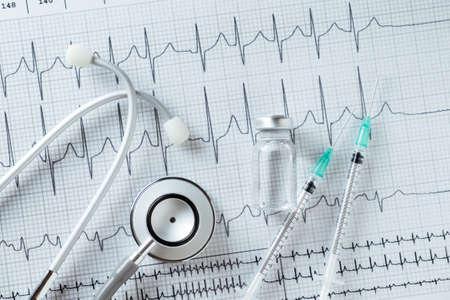 ampules: Stethoscope medical ampules and syringe on EKG graph background Stock Photo