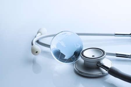 Global healthcare. Globe and stethoscope blue tone on white background