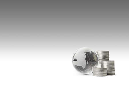 globe and silver coins on gray background 免版税图像
