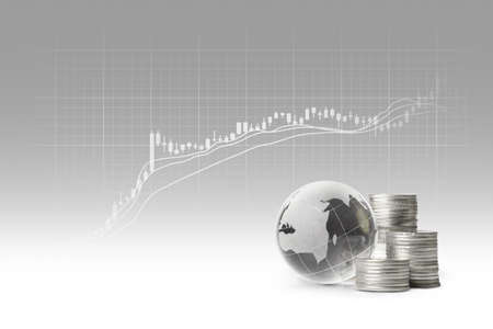globe and silver coins and Stock Charts on gray background