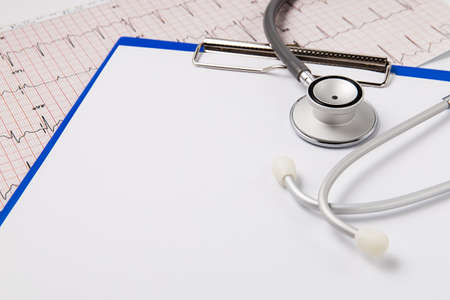 Stethoscope blue clipboard with a few sheets of paperand and cardiogram