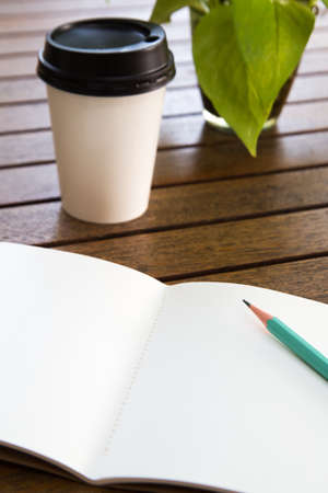 Notebooks, pencils, coffee cups on a wooden table