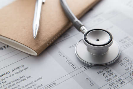 Notebooks, pen, Stethoscope on the document. Financial concept