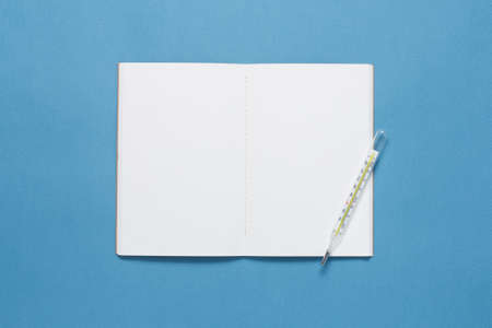 Notebook and thermometer on blue background