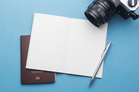 Essentials for travelling including notebook passport camera and pen on blue background 免版税图像