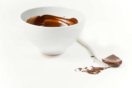 The picture of the wooden spoon just used top stir the melted dark chocolate Stock Photo