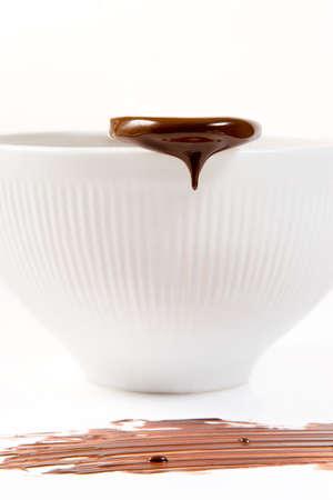 木のスプーンから滴り落ちる溶かしたダーク チョコレート