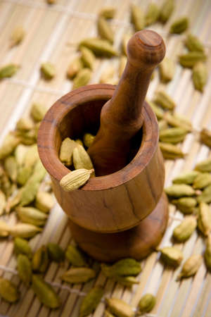 Wooden mortar with green cardamom seeds Stock Photo