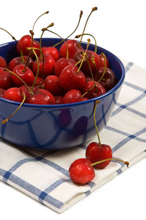 Sweet cherries in the blue cups on white background