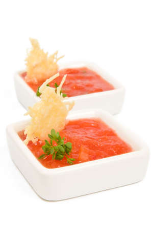 White bowl of tomato sauce with cheese chips