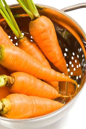 Fresh carrots in the colander on white background Stock Photo