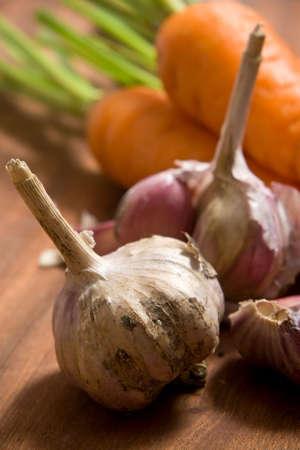 Fresh garlic and carrot on cutting board