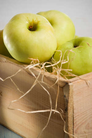 Green apples in the  wooden box