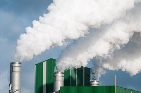 The pipes of a bio ethanol factory with white smoke as a global warming concept.