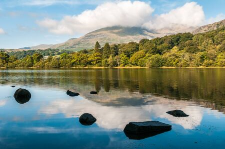 An early morning view of Coniston Water in the English Lake District. The summit of Coniston Old Man in the background is hiding in the clouds. Stock Photo