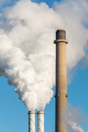 The pipes of a coal power plant with white smoke as a global warming concept.