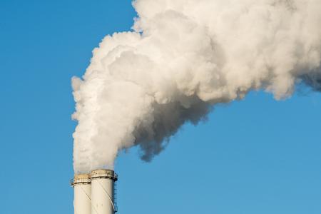 De pijp van een kolencentrale met witte rook als een opwarmingskoncept. Stockfoto