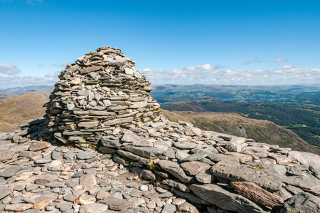 Summit cairn on the top of Coniston Old Man in the English Lake District.  The view of the surrounding landscape includes lake Windermere in the distance.