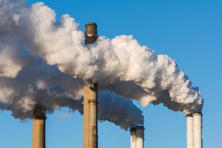 De schoorstenen van een krachtcentrale met enorme rookstapels en een blauwe hemel als achtergrond.