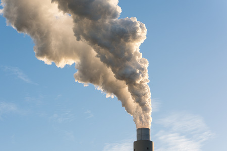 The pipe of a coal power plant with grey smoke against a blue sky as a global warming concept.