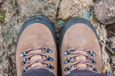 A pair of brown hiking boots on wet rocks in the outdoors.