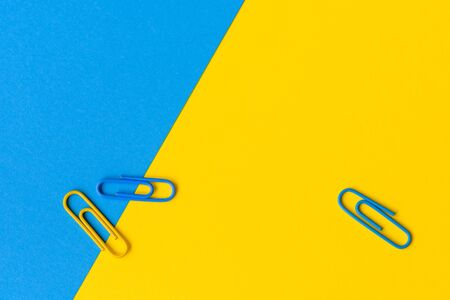 Office concept with two blue and one yellow paperclip isolated against a blue and yellow background with copy space.