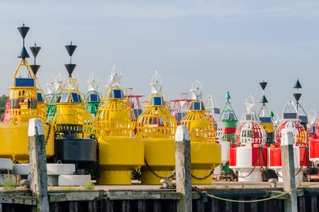 Colorful navigation buoys are standing on the quay at the depot on the dutch wadden island Terschelling. Reklamní fotografie