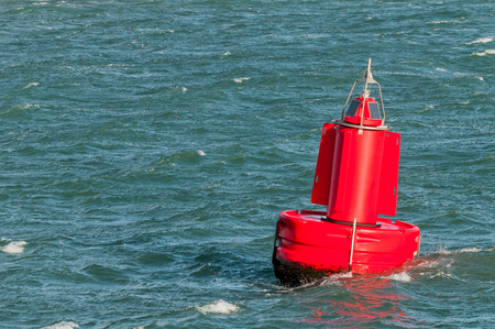 A red buoy is floating on the water surface in the Port of Rotterdam in the Netherlands.